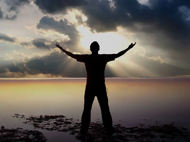 Person standing with arms outstretched viewing beautiful sunrise over a body of water