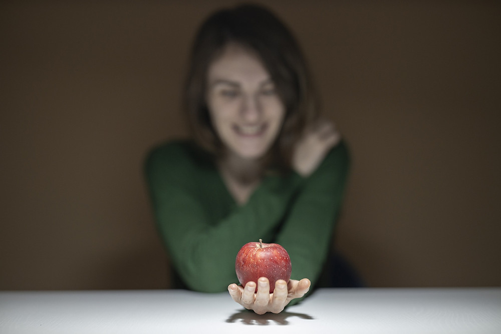 woman holding a red apple and smiling at it