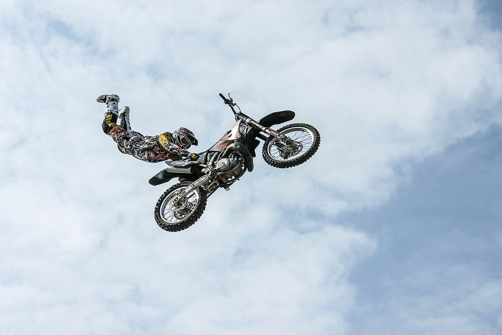 Man holding onto seat of motorcycle as it flies through the sky, clouds in background
