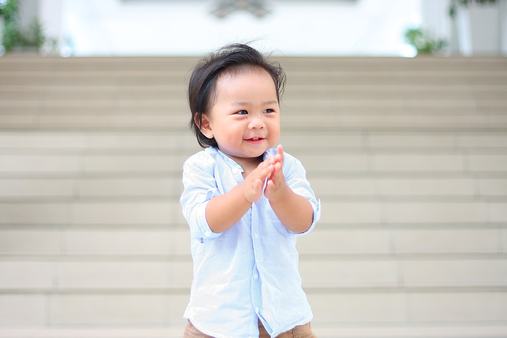 little boy clapping his hands in front of many stairs