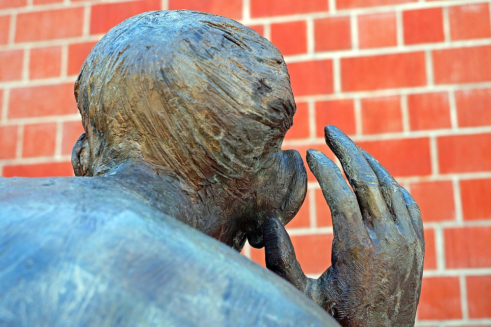 back of bronze statue with hand up to ear as if trying to hear better