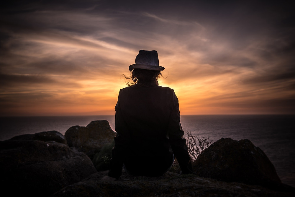 person sitting on a rock, viewed from behind, they are looking at a sunrise or sunset over a lake or an ocean