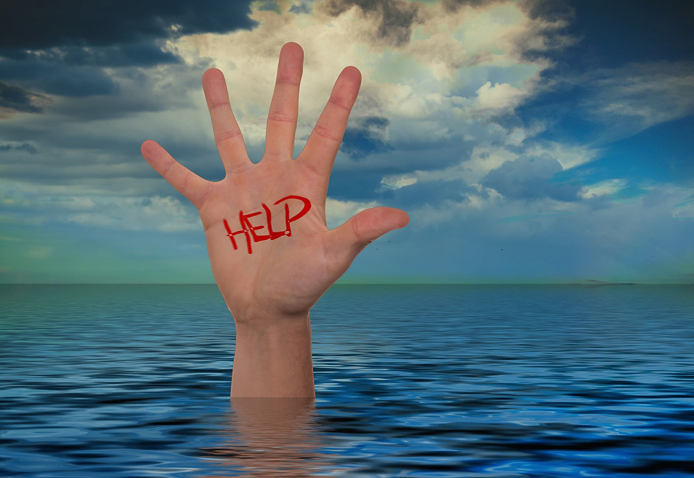 "hand raising up out of the water, the word ""help"" written on the palm"
