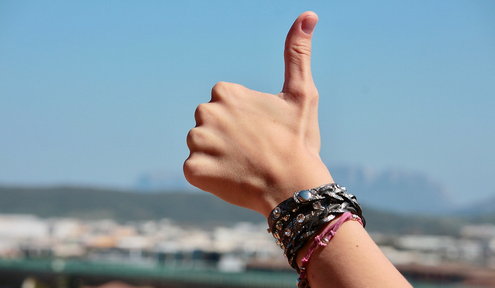 hand in a thumbs up sign with blurred background