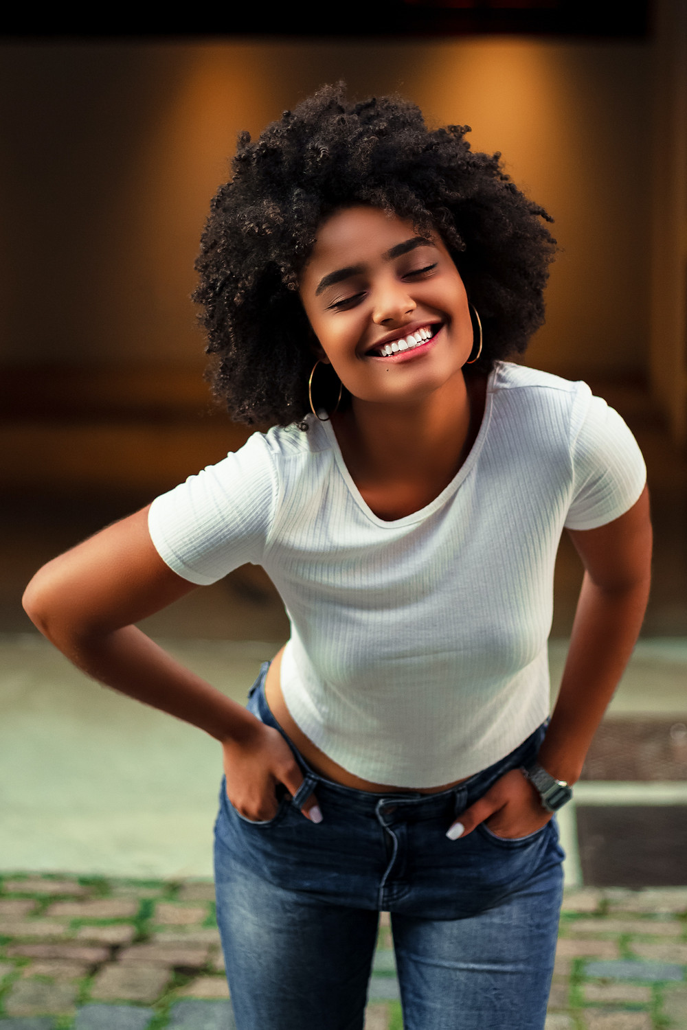 woman in jeans and white shirt leaning forward and smiling