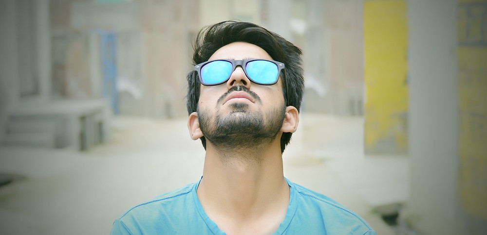 Man in a t-shirt with short beard and sunglasses looking up