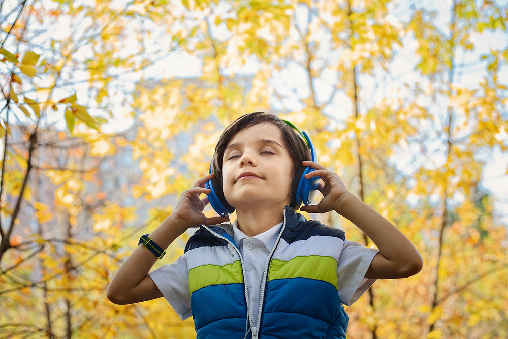 Young boy standing among trees with yellow leaves, eyes closed, listening to headphones