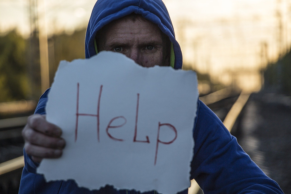 """man holding sign with """"help"""" written on it"""