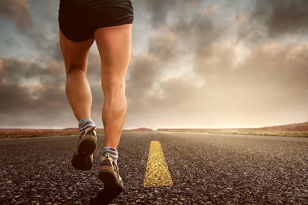 runners legs from behind, on a road with nothing else, the road disappearing into the horizon