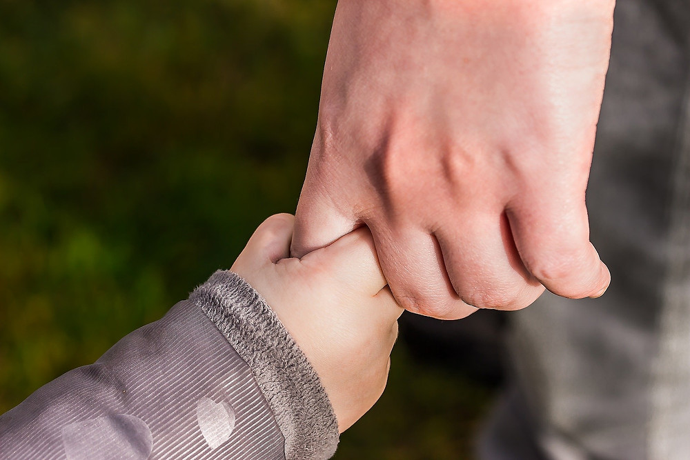 Adult finger being held by child's hand