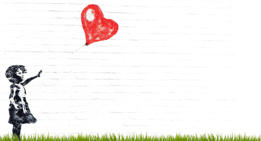 drawing on a brick wall of little girl reaching for a heart shaped balloon that is flying away