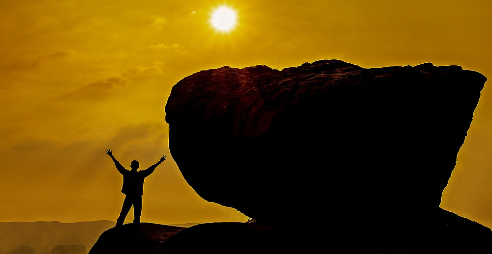 silhouette of a man standing on a high rock or mountain next to a large boulder, his arms are outstretched, he's looking at a sunrise or sunset