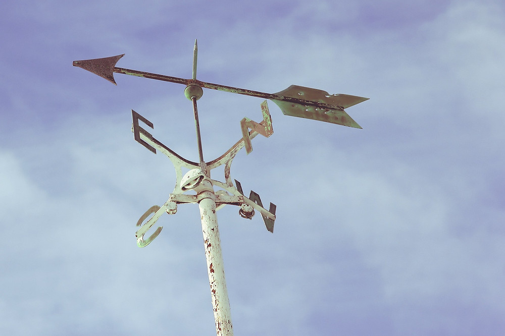 A North-South-East-West weathervane with arrow pointer against clouds in the sky
