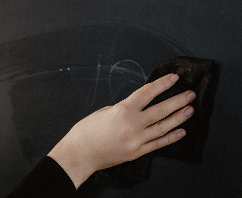 a hand with eraser wiping a blackboard clean (Photo by cottonbro from Pexels)