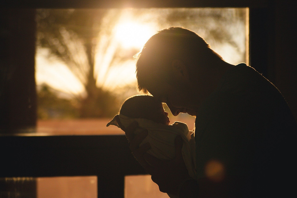 man holding baby, foreheads together, sun shining in background