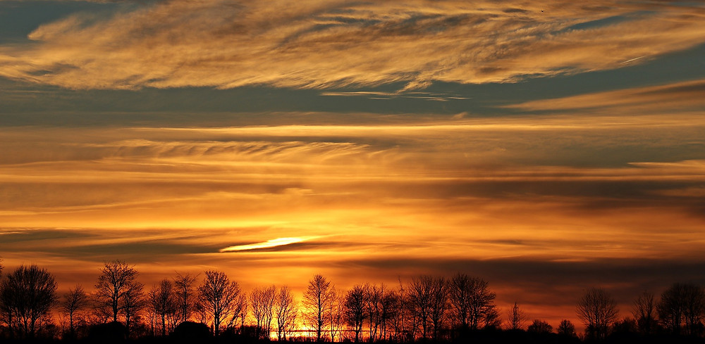 Sunset with huge amount of sky and a small horizon showing a silhouette of trees