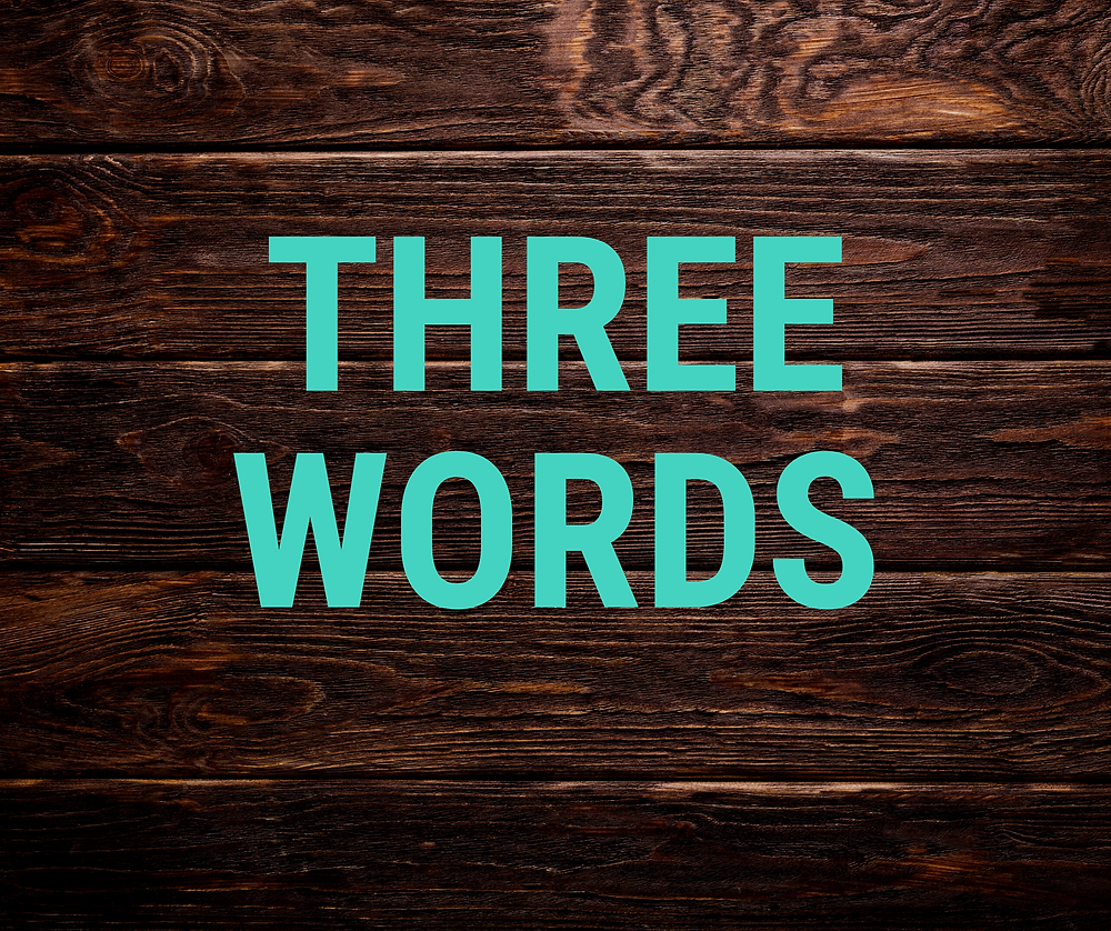 """""""Three Words"""" printed on top of a wood-paneled background"""