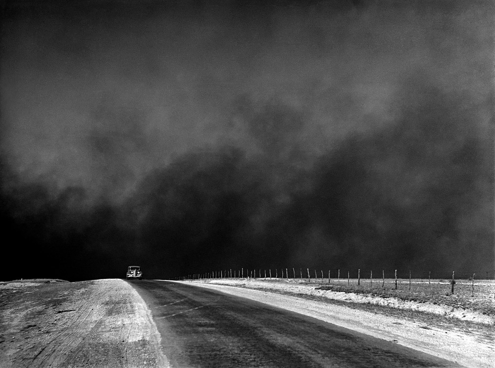 old truck alone on road with dust cloud behind
