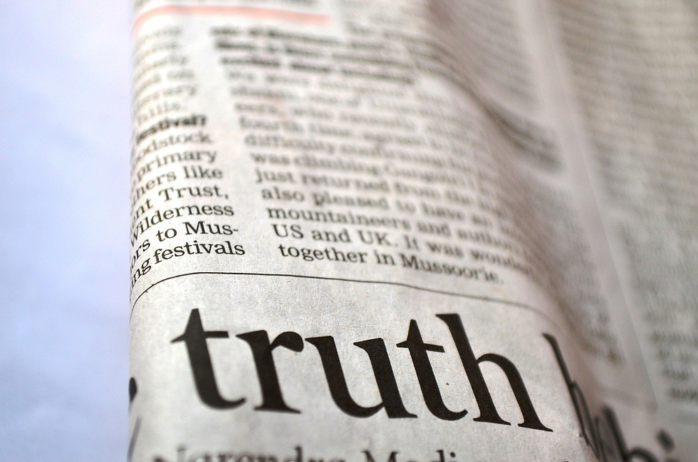 """newspaper with focus on the word """"truth"""" in large print"""