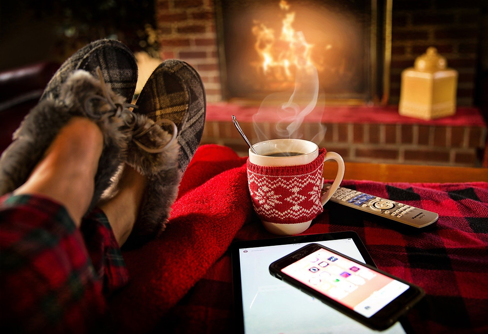 feet in slippers, propped up on a blanket, a mug of something warm on a table nearby, a fireplace in the distance