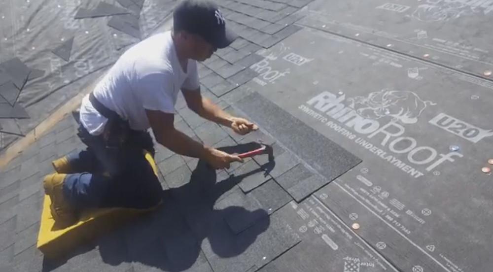 Professional roofer installing shingles