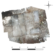 Drone photograph of Structure 168-1 excavations with vertical excavations in front and within the building itself.