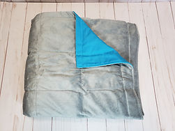 light grey chenille weighted blanket folded with flap flipped over to show turqouise side