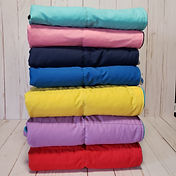 folded pile of 7 different colored weighted blankets