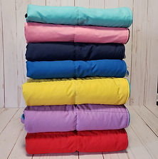 folded pile of 7 different coloured weighted blankets