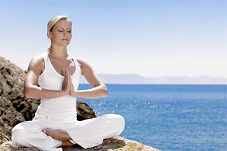 Yoga girl on a clif by the sea
