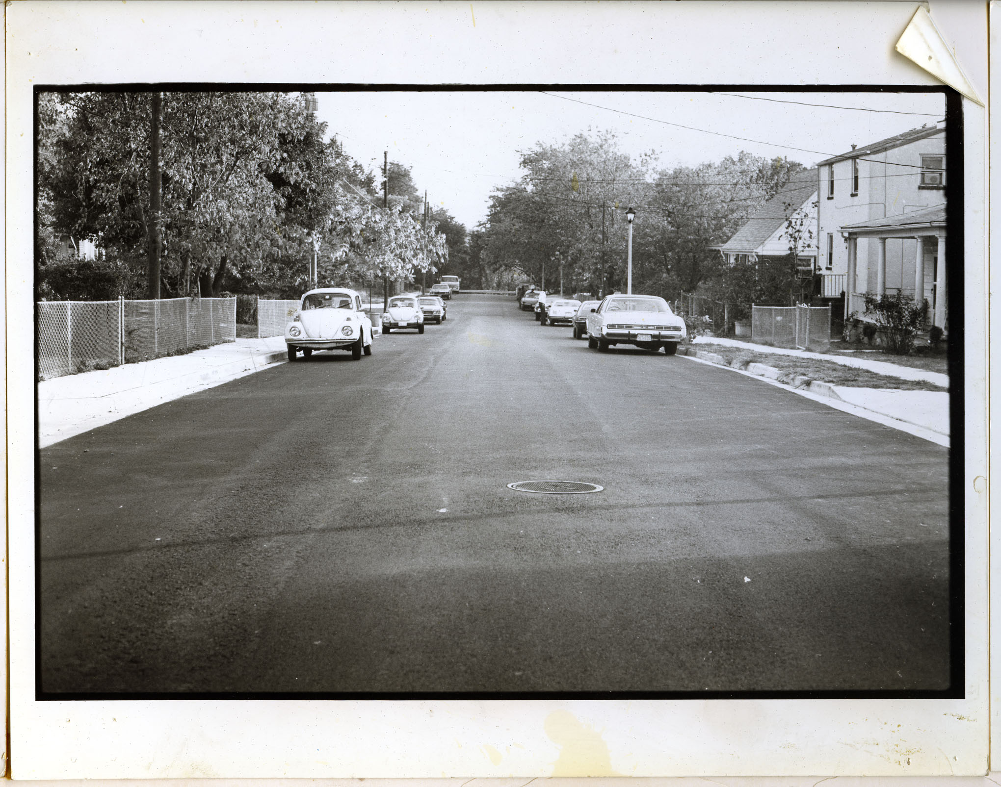 Street scene. Cars line the road. Some houses visible, as well as trees and chain link fences. arlin