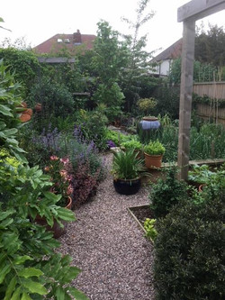 Informal garden with gravel paths, structures and raised vegetable beds