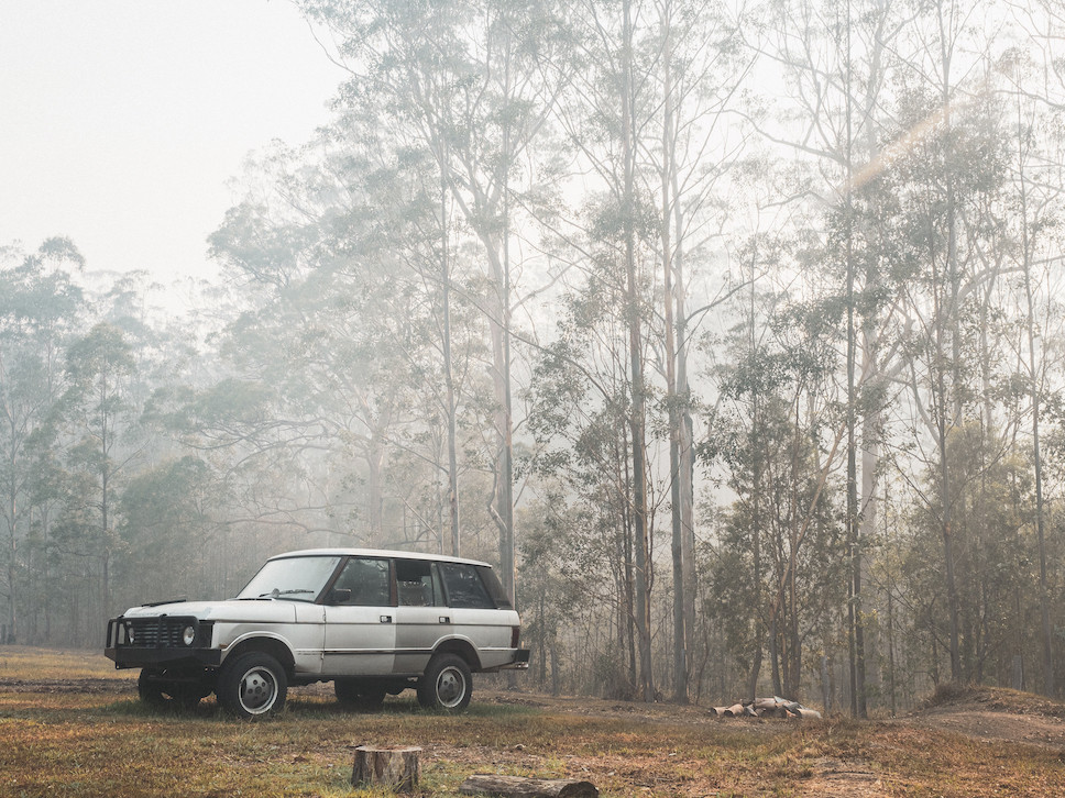 Range Rover in the bush, surrounded by smoke haze.