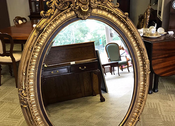 A large gold gilt oval bevelled mirror
