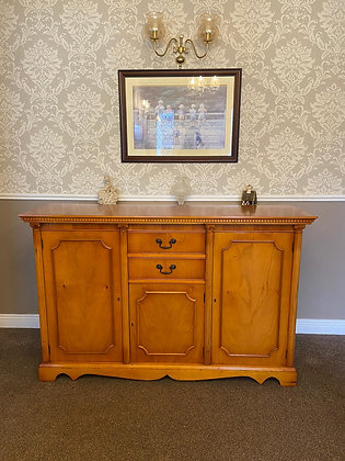 Yew break front sideboard with craved edging