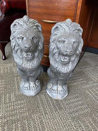 A pair of painted concrete lion garden ornaments.