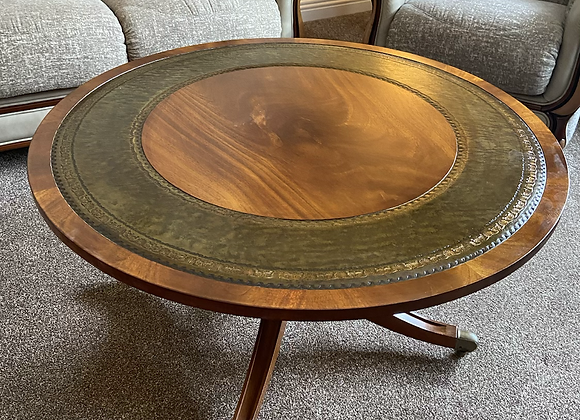 Mahogany round occasional table with green leather top on caster wheels
