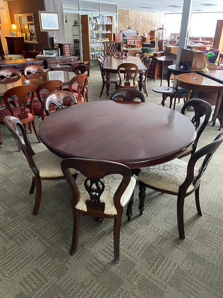 Solid mahogany round dining room table standing on caved pod stand with 6 chairs