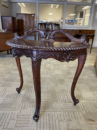 Ornate console table with scrolled back piece on cabriole leg