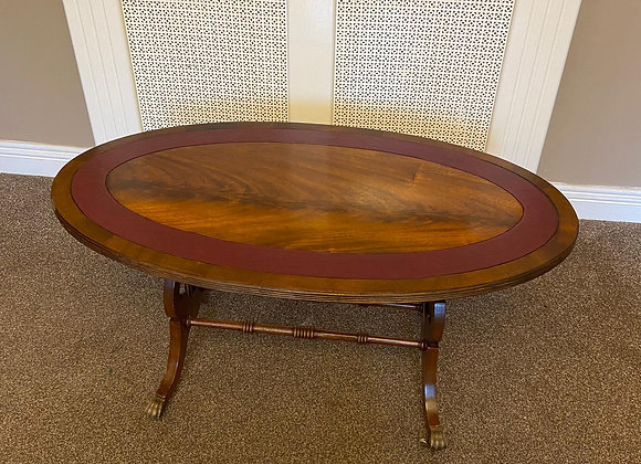 Mahogany oval coffee table on caster wheels with red leather inlaid