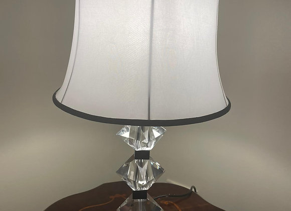 A stunning black and clear crystal lamp with a white lamp shade