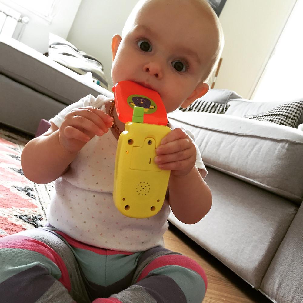 un bebe mordiendo un móvil de juguete..