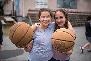 Two girls holding basketballs