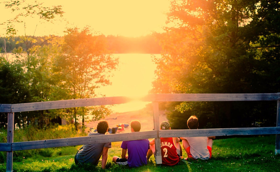 Group of boys sitting on a hill overlooking the lake at sunset. Click on sign up to register for camp or learn more for more information about camp.