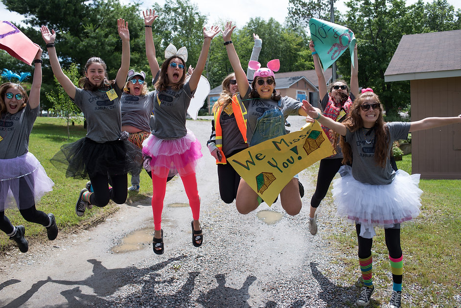 Staff members dressed in costumes jump excitedly in the air.