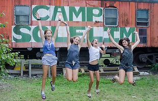 Girls jumping in front of camp sign
