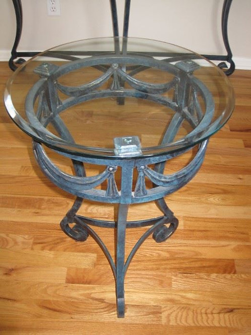 "Glass top heavy wrought iron side table, 18"" tall by 25"" across"