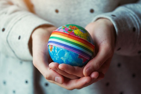 woman's hands holding globe with LGBT ra