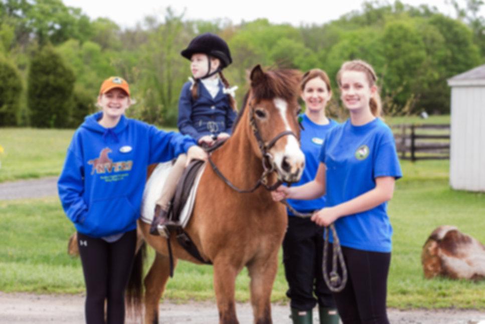 Image: NVTRP volunteers assisting a rider while horseback riding.