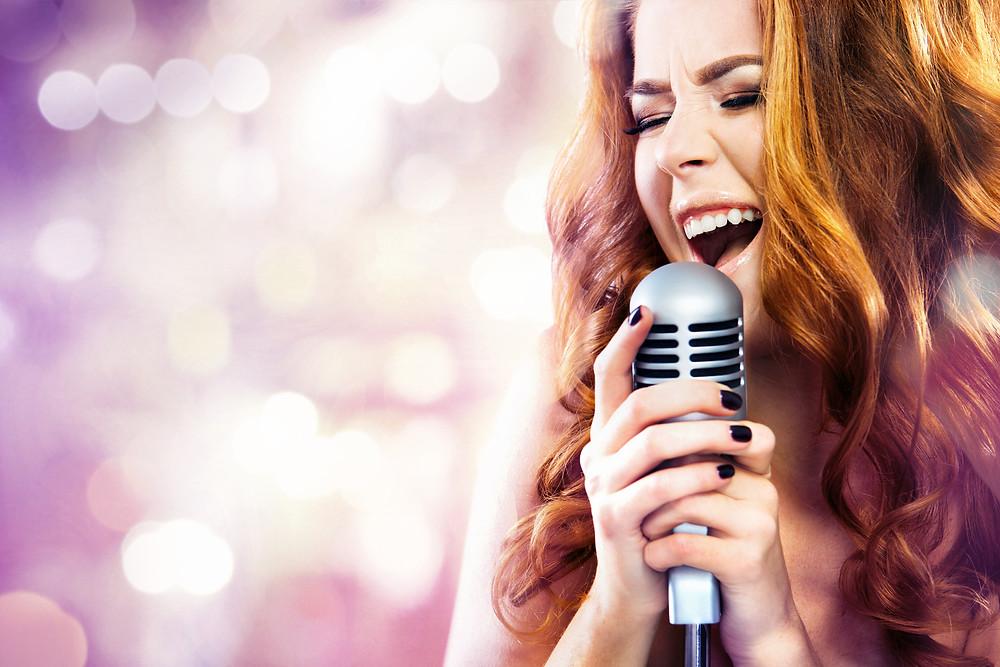 foto ilustrativa de uma mulher segurando um microfone e cantando